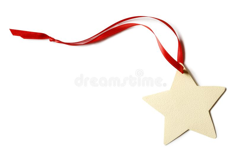 Blank, star-shaped Christmas gift tag with red ribbon isolated on white background. Simple, rustic, artisanal, country-style holiday crafts decorations stock photo