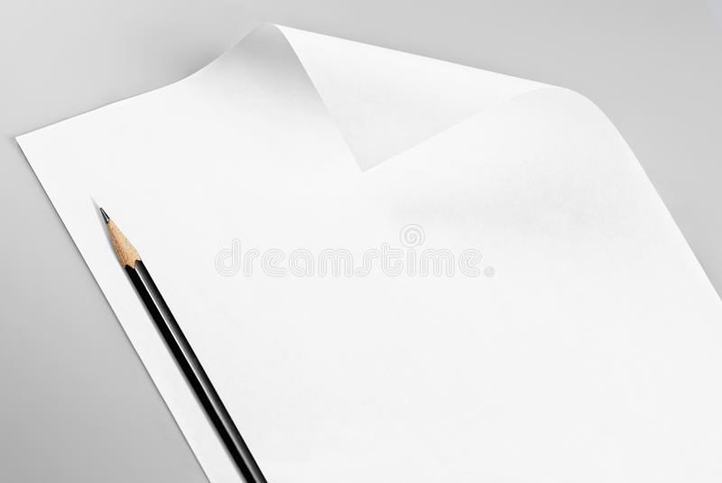 Blank stationery: sheet of paper with curled corner and pencil stock photography