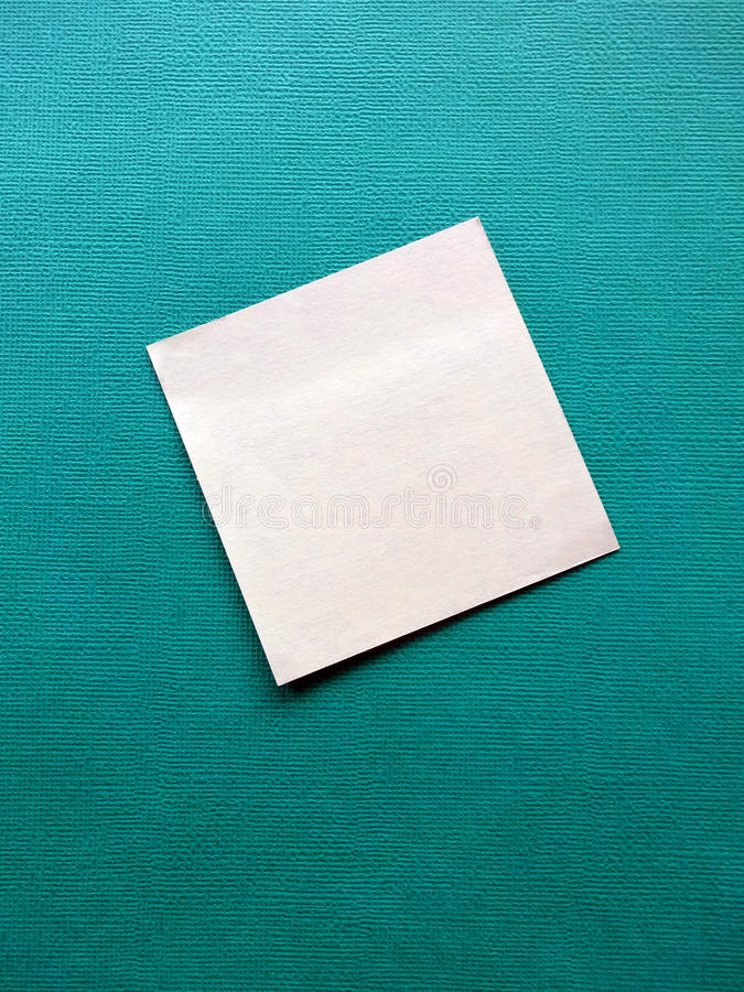 Blank Sticky Note. A blank sticky note attached to a green background stock photography