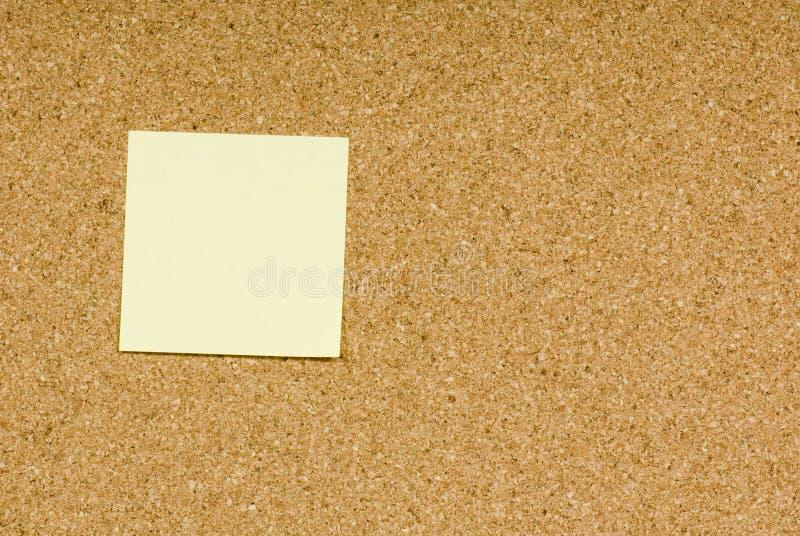 Blank sticky note. On a cork bulletin board stock image