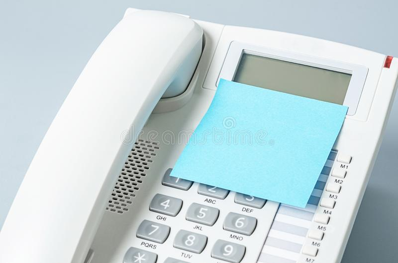 Blank sticky note on the telephone. For your text or message stock photos