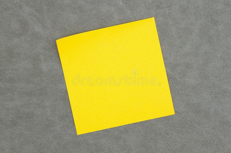 Blank sticky note on textured gray leather. You can use as a mockup for your message stock image