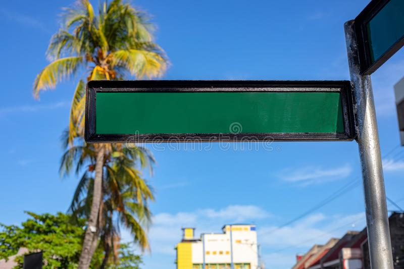 Blank street sign on sunny urban landscape with palm trees and yellow building. Green metallic sign plate on pillar stock image