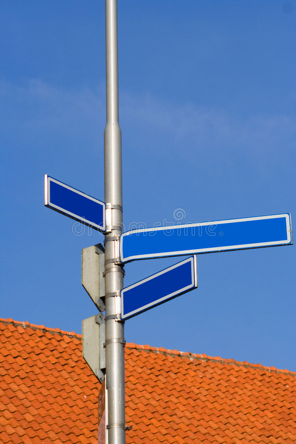 Blank street signs. A view of blank street signs at an intersection with an orange tiled roof and blue sky in the background stock photography