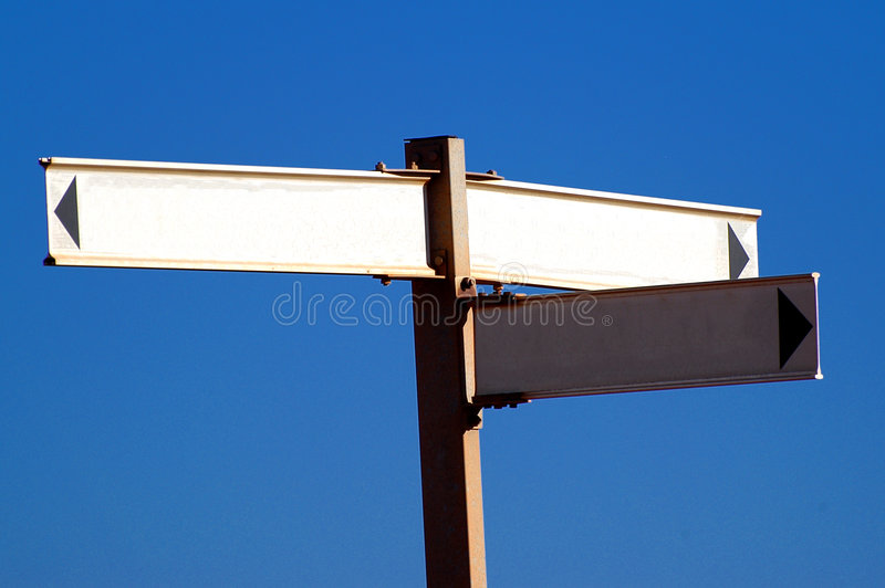 Blank street signs. A closeup view of blank street signs against a blue background royalty free stock image