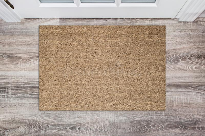 Blank tan colored coir doormat before the white door in the hall. Mat on wooden floor, product Mockup royalty free stock photos