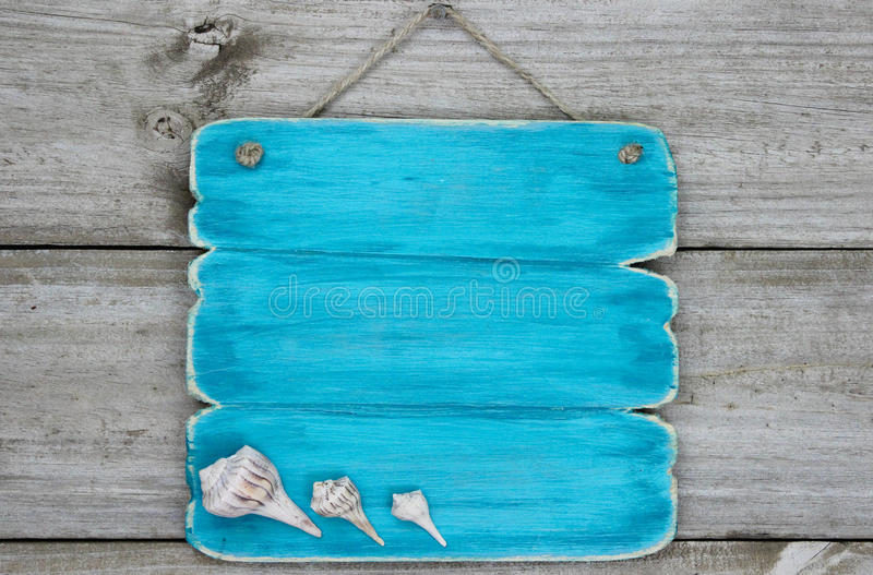 Blank teal blue sign with seashells hanging on rustic wooden door. Blank bright teal blue sign with seashells hanging on rustic wooden background stock photos