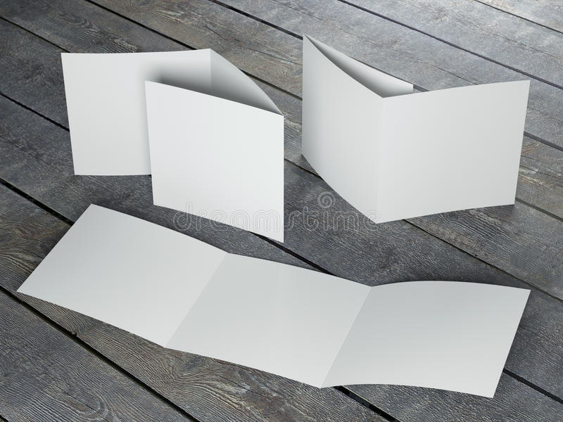 Blank template of trifold square brochure. On wood floor royalty free illustration