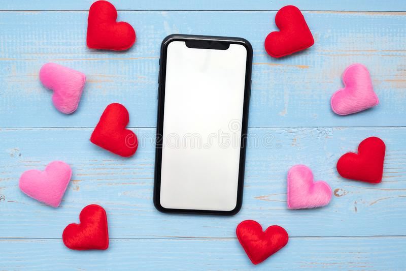 Blank touchscreen display of black smart phone with red and pink hearts shape decoration on blue wooden table background. Love,. Romantic and Holiday concept stock photo