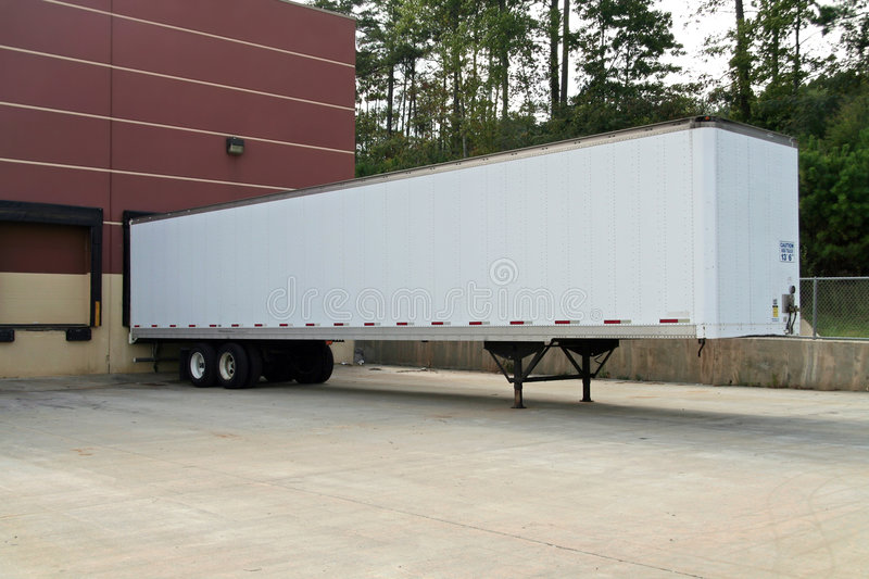 Blank tractor trailer parked at the loading dock. Trailer is plain white for your own text or logo royalty free stock photography