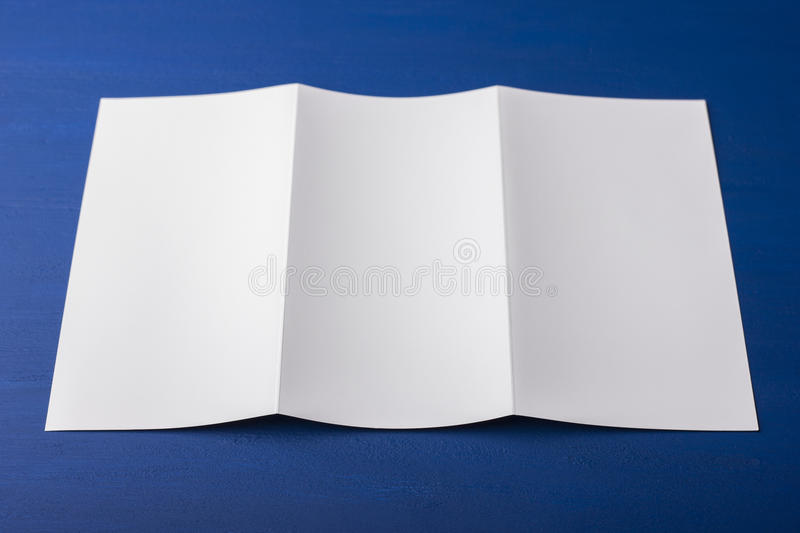 Blank tri fold brochure on blue background to replace your design or message. A mock-up for brand identification for designers royalty free stock images