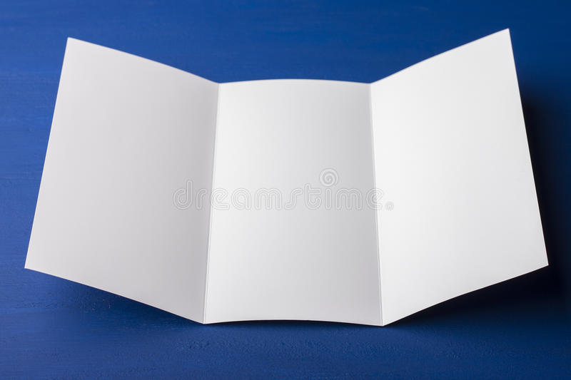 Blank tri fold brochure on blue background to replace your design or message. A mock-up for brand identification for designers royalty free stock image