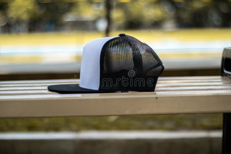 Blank trucker hat cap flat visor with black and white color. In outdoor, ready for your mock up design or presentation your design project stock photos
