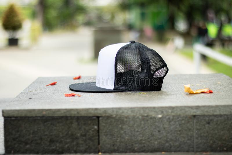 Blank trucker hat cap flat visor with black and white color. In outdoor, ready for your mock up design or presentation your design project royalty free stock image