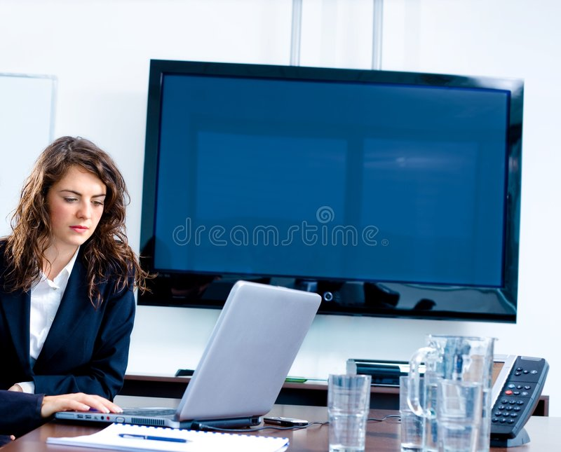 Blank TV screen at office. Young businesswoman sitting by meeting table at office in front of a huge blank plasma TV screen and using laptop and phone royalty free stock photography
