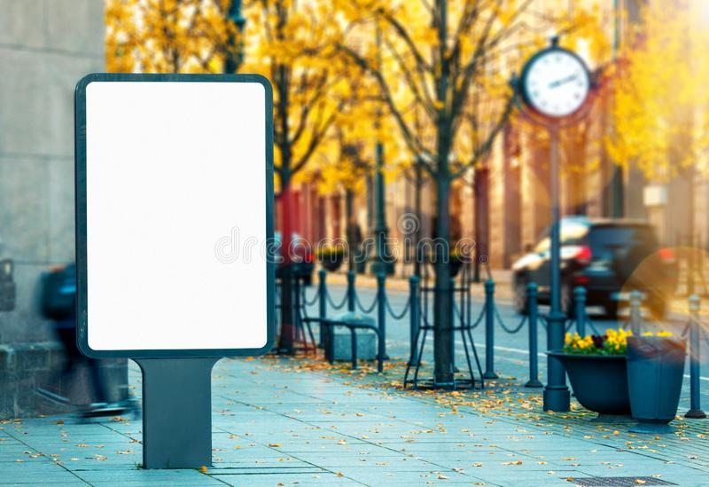 Blank vertical outdoor billboard mockup on city street. On bright vibrant autumn day stock images