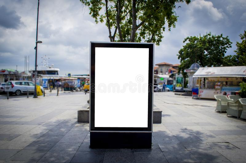 Blank vertical outdoor billboard mockup on city street. On bright vibrant autumn day royalty free stock photo