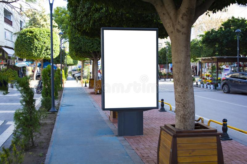 Blank vertical street billboard stand with city background. Blank street billboard poster stand on city background. 3d illustratio royalty free stock photos