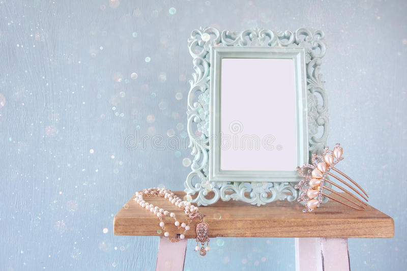 Blank victorian style frame, pearls necklace and hair decoration. Blank victorian style frame, white pearls necklace and hair comb decoration on wooden table stock image