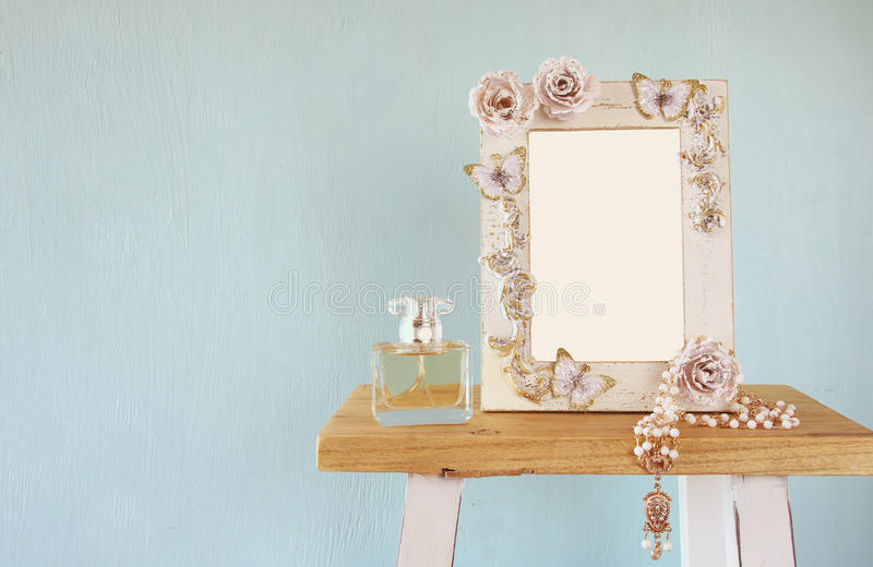 Blank victorian style frame, perfume bottle and necklace. On wooden table. Ready to photograph montage royalty free stock images