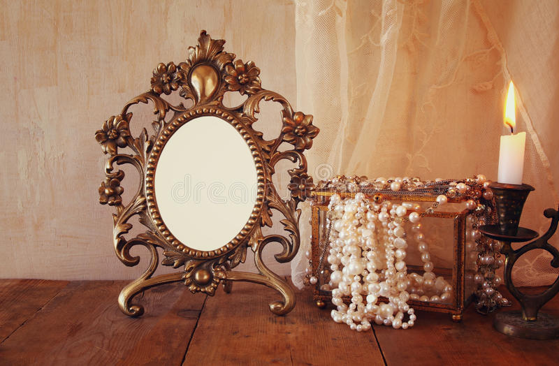 Blank vintage frame, pearls and burning candle stock photo