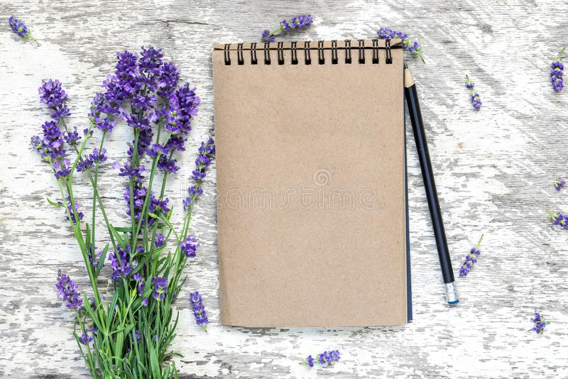 Blank vintage notepad with lavender flowers bouquet and pencil over white wooden table. top view. mock up stock image
