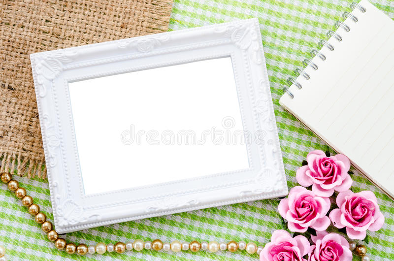 Blank vintage white photo frame and open diary with pink rose on stock photo