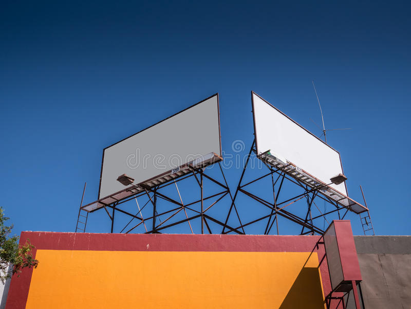 Blank white billboards. Two blank white billboards on rooftop against blue sky background royalty free stock images
