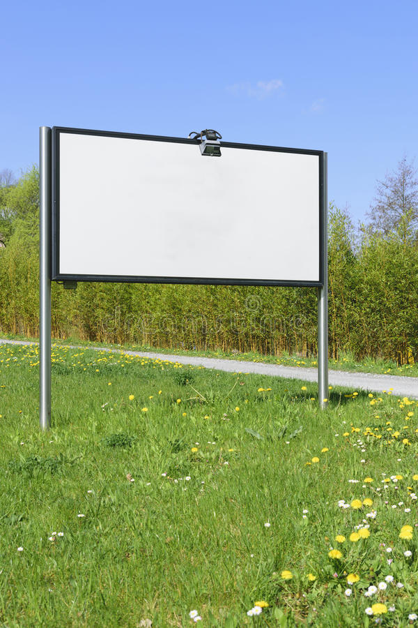 Blank white board on meadow royalty free stock photography