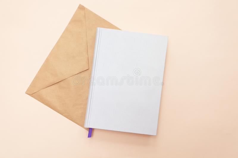 Blank white book with brown envelope on the pale pink background. Flat lay. Mock up of closed blank notebook of white color and brown envelope a beige background royalty free stock image
