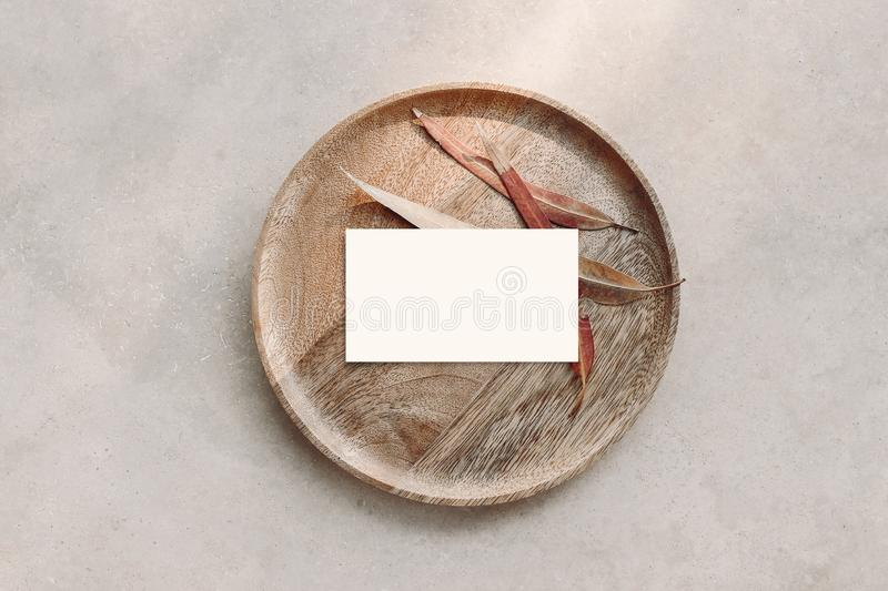 Blank white business card mockup on wooden plate. Marble backgound with dry colorful eucalyptus leaves. Modern template stock photography