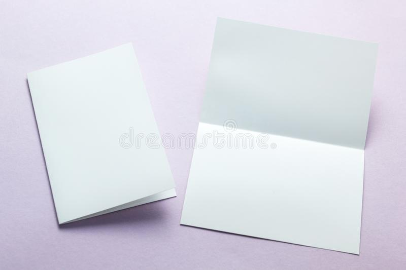 Blank white business card postcard flyer isolated on a purple background, mockup.  stock photo