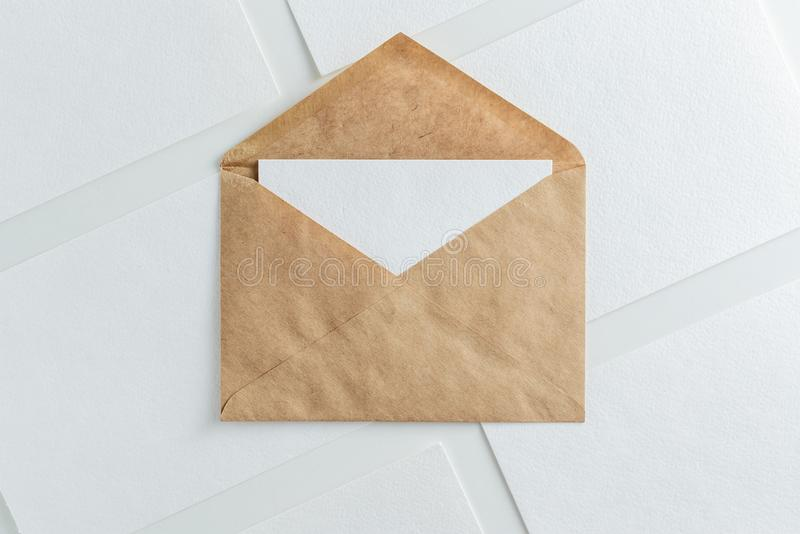 Blank white card in kraft brown envelope and paper sheets template mock up stock photo