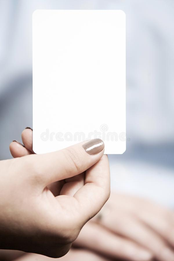 Card blank and white, woman is holding it with her fingers stock photo