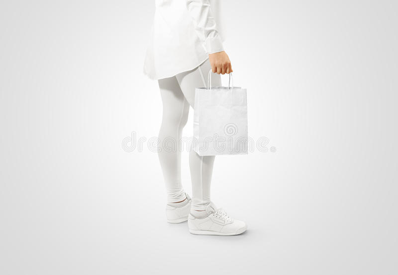 Blank white craft paper bag design mockup holding hand. Woman hold kraft textured purchase pack mock up . Clear shop bagful branding template. Shopping carry stock images