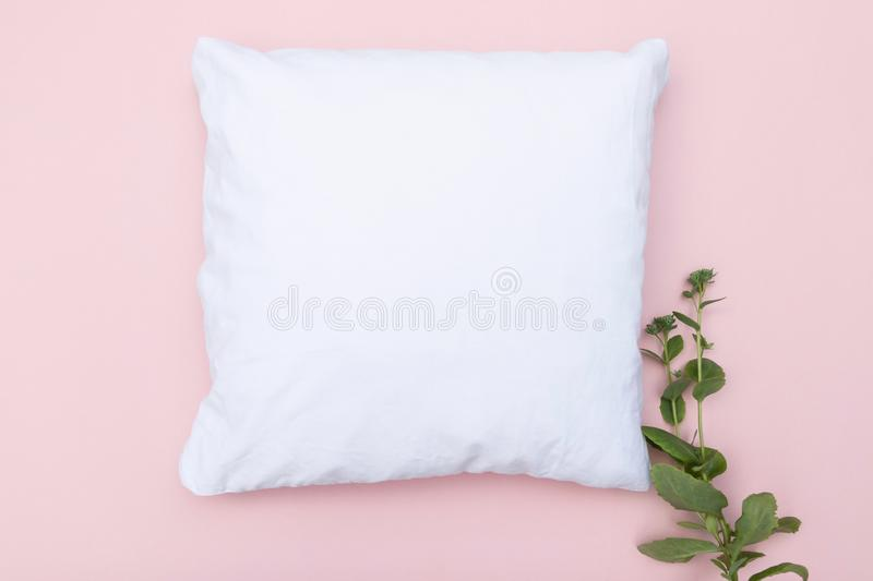 Blank white cushion mock up on a pink background and green plant. Empty for own design royalty free stock photos