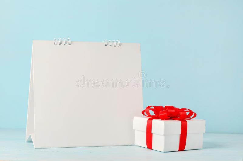 Blank white desk calendar and Christmas gift box with red ribbon. Bow on blue wooden background royalty free stock images