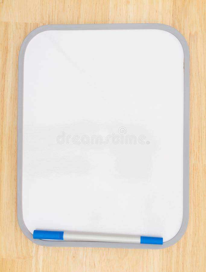 Blank white dry erase board with marker on wood textured background. With copy space for your message royalty free stock image