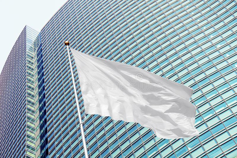 Blank white flag on pole waving in the wind against modern office building. Blank white corporate flag on pole waving in the wind in the background of modern royalty free stock image
