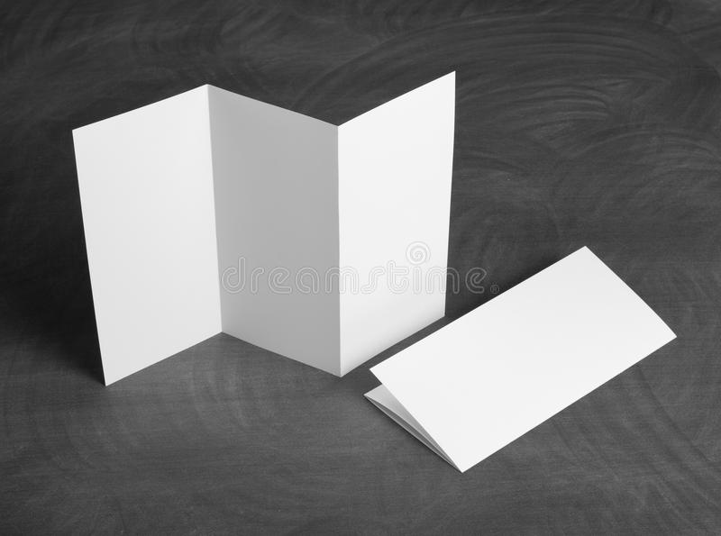 Blank white folding paper flyer on a black chalkboard. Identity design, corporate templates, company style, set of booklets, blank white folding paper flyer on a royalty free stock images