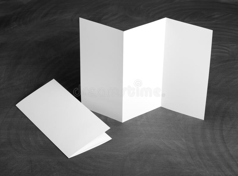 Blank white folding paper flyer on a black chalkboard. Identity design, corporate templates, company style, set of booklets, blank white folding paper flyer on a royalty free stock image