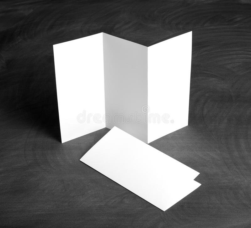 Blank white folding paper flyer on a black chalkboard. Identity design, corporate templates, company style, set of booklets, blank white folding paper flyer on a royalty free stock photos