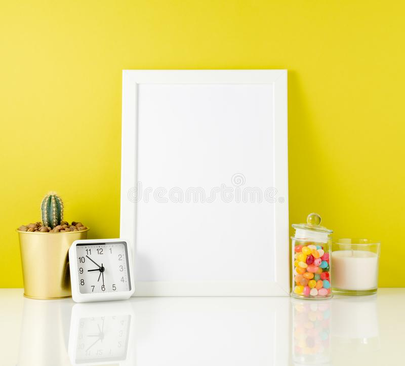 Blank white frame, clock, succulent, candy on a white table against the yelloow wall. Mockup with copy space. stock photos