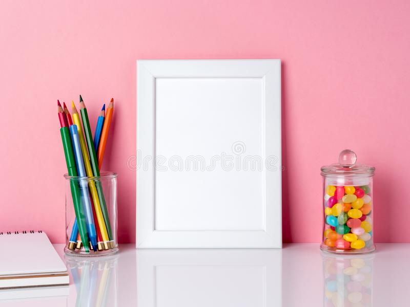 Blank white frame and crayon in jar, candys on a white table against the pink wall with copy space royalty free stock image