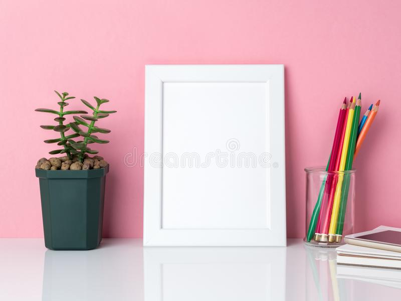 Blank white frame, crayon in jar, plant cactus on a white table royalty free stock photos