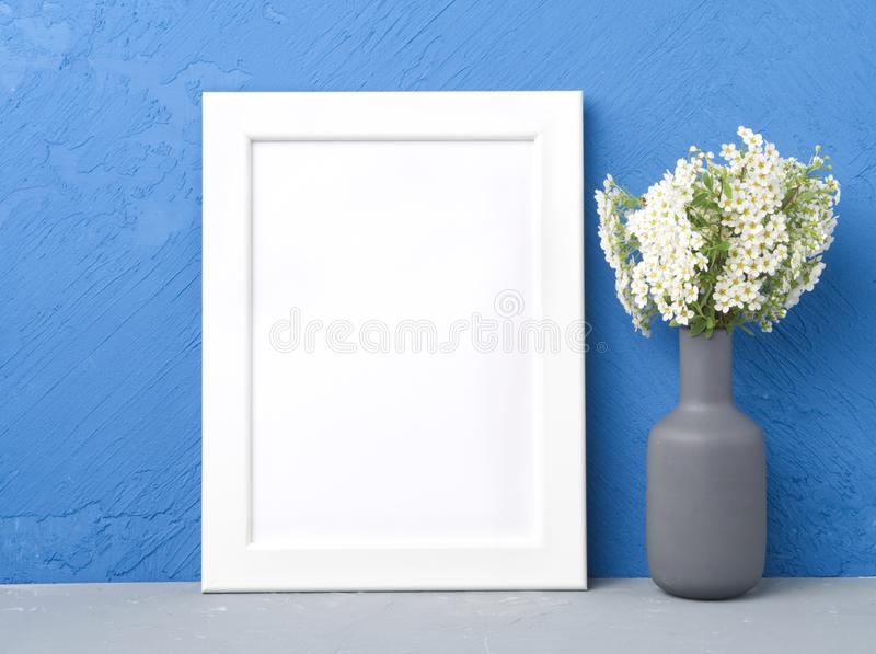 Blank white frame, flower in vaze on gray table against dark blue concrete wall with copy space. Mock up. royalty free stock images