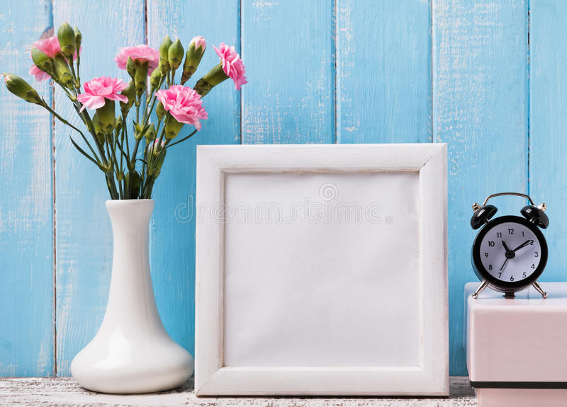 Blank white frame, pink flowers and alarm clock. Mock up stock photography
