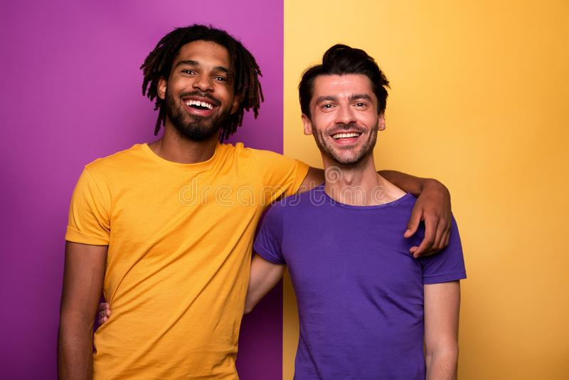 Blank and white friends. Concept of integration, union and partnership. Yellow and violet background royalty free stock images