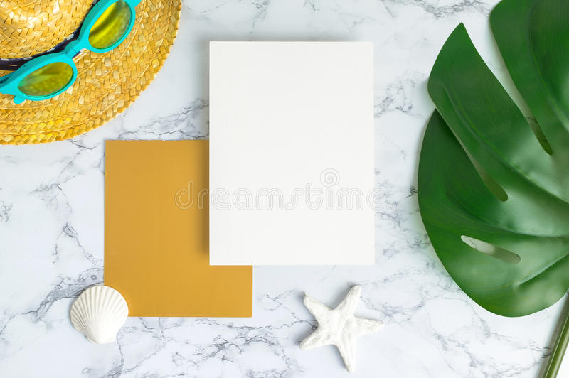 Blank white and gold paper card on marble table top view with summer beach accessories and shell,starfish,tropical palm leaves royalty free stock image
