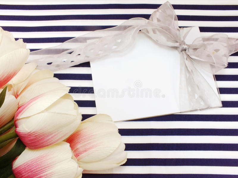 Blank white greeting card with beautiful artificial flowers and empty tag for your text. Stylish branding mockup with flowers to display your artworks stock photo